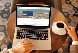First National Bank of South Padre Island website displayed on laptop computer in coffee cafe