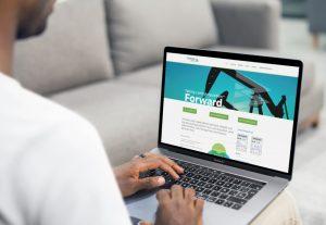 Forward Land homepage displayed on male users MacBook laptop
