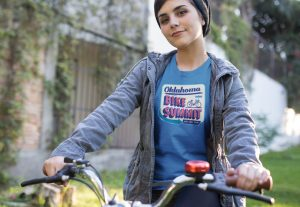 Young adult female on bicycle wearing Oklahoma Bike Summit T-Shirt