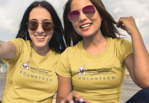 Two females taking a selfie wearing yellow Ronald McDonald House Charities Volunteer shirts
