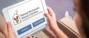 Ronald McDonald House Charities Chicagoland Logo displayed on iPad being held by female user