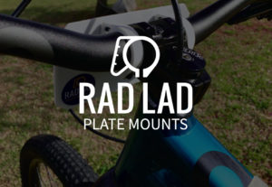 Rad Lad Plate Mounts Logo over darkened photo of a bicycle handlebar with plate mounts installed