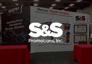 S&S Promotions Logo over darkened photo of trade show booth designed by Hester Designs