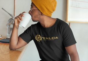 Young black male drinking coffee at cafe wearing Taloa Music Festival shirt